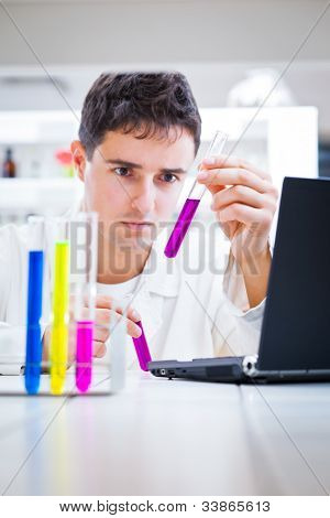 close-up portrait of a young male researcher carrying out experiments in a chemistry research lab (color toned image)