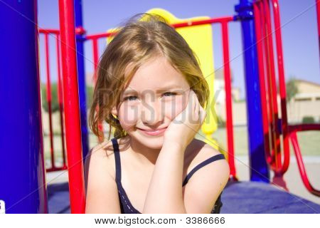 Six Year Old Girl Smiling With Playground In Background