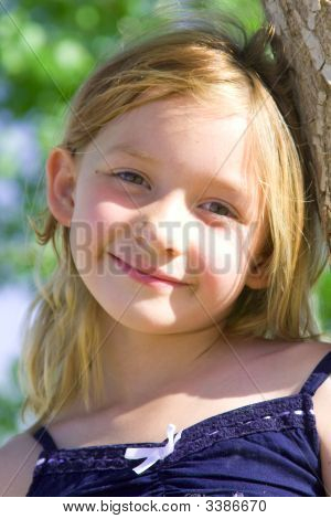 Six Year Old Girl Smiling Leaning Against A Tree