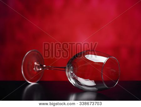 Empty Wine Glass Lying On Its Side. A Glass Of Wine. Beautiful Glass Wine Glass On A Red Background.