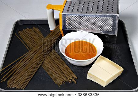 Black Tray With Spicy Spaghetti, Italian Cheese, Tomato Sauce And A Scratcher