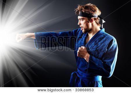 Martial arts fighter posing at studio.