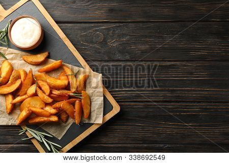 Slices Of Baked Potato Wedges, Rosemary, White Sauce, Kitchen Board On Wooden Background, Space For