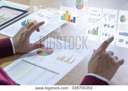 Businessman Interacts With Augmented Reality Graphics While Deeply Reviewing A Financial Report For