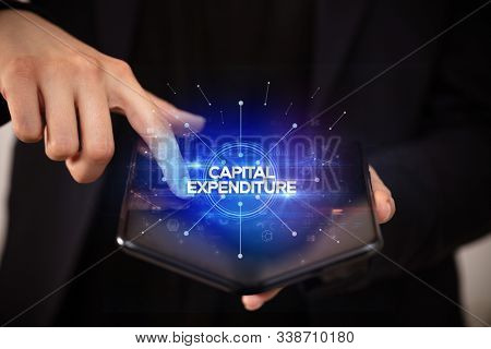 Businessman holding a foldable smartphone with CAPITAL EXPENDITURE inscription, new business concept