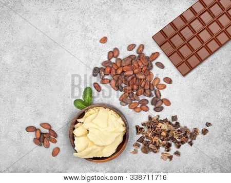 Bar Of Milk Chocolate, Cocoa Butter, Carob, Cocoa Beans And Mint On Gray Stone Background. Top View