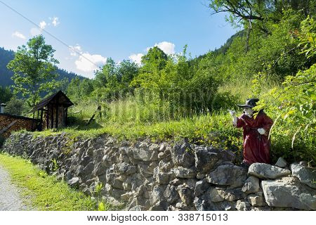 Location: Vlkolinec In Slovakia. Ceramic Figurine Of A Witch In Red Attire, In The Mountain Village