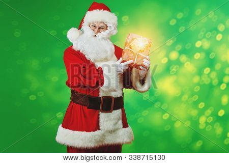 Jolly Santa Claus wishes everyone a Merry Christmas with box gift in his hand. Studio portrait on a green background.
