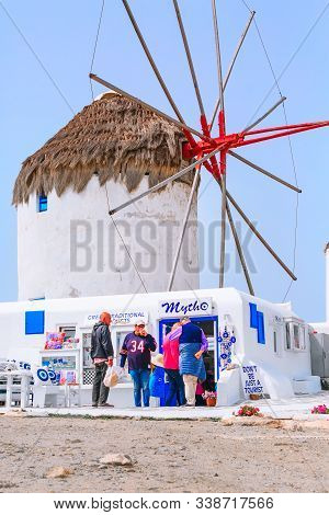 Mykonos, Greece - April 23, 2019: People, Greek Iconic Windmill View And Gift Shop In Famous Island