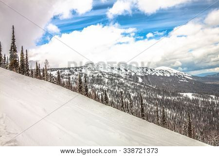 Winter Mountain Landscape. View From The Slope Of The Mountain. Spruce Taiga Under The Snow Against