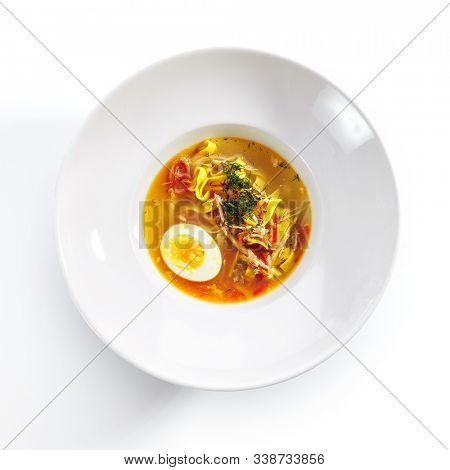 Chicken soup with tagliatelle pasta, eggs and fresh herbs isolated on white background top view. Delicious restaurant clear bouillon with poultry meat, vegetables and spices