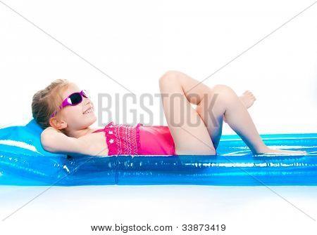 schattig klein meisje in een pak zwemmen op een opblaasbare matras