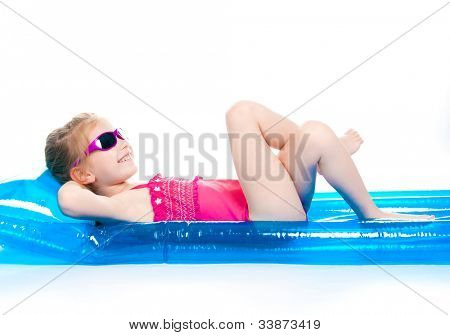 niña linda en un traje de baño en un colchón inflable