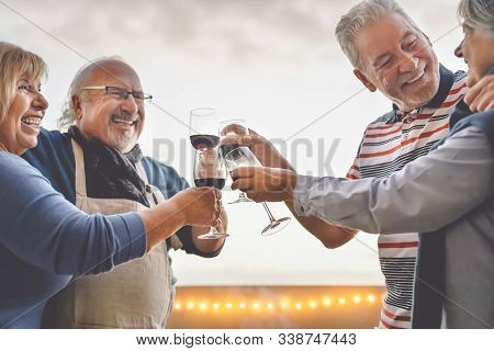 Happy Seniors Friends Drinking Red Wine On Terrace Sunset - Mature People Having Fun Laughing And Sh