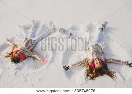 Smiling Children Lying On Snow With Copy Space. Funny Kids Making Snow Angel. Children Playing And M