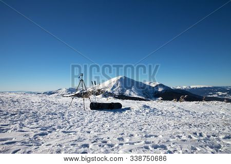 Tripod For Photography Camera, Ski Poles, Snowboard On Snow And Snow-capped Mountains At Sunny Winte
