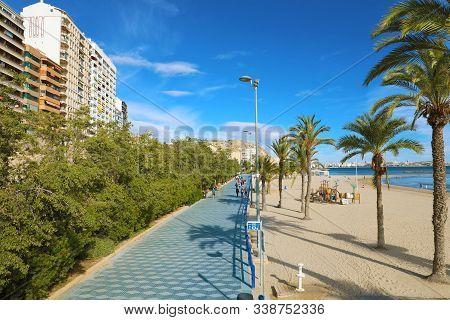 Alicante, Spain - November 29, 2019: Alicante Promenade Paseo De Gomiz With Playa Del Postiguet Beac