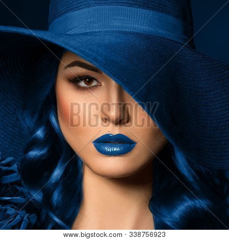 Portrait Of A Beautiful Woman With Blue Lips In A Hat, Toned In Color Of The Year 2020, Classic Blue