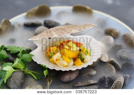 Scallop Tartare With Mango And Cherry Tomatoes, Served In A Plate On Stones With Dry Ice.