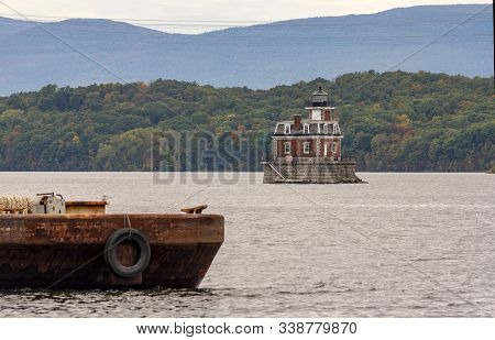 A Rusty Old Barge Sits In The Foreground Near The Hudson Athens Lighthouse In Upstate New York Usa