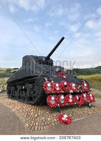 Sherman tank at Slapton Sands, Devon,UK covered in red poppy wreaths commemorating D Day landings in 2nd World War. It stands as a memorial to UK & US soldiers who lost their lives 70 years on in 2019