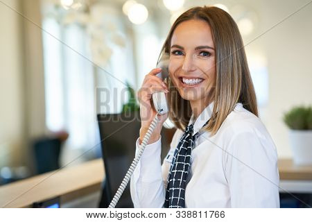 Receptionist answering phone at hotel front desk