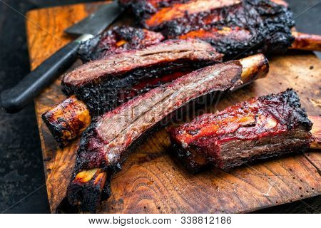 Barbecue burnt chuck beef ribs marinated with hot chili sauce sliced as closeup on an old rustic wooden cutting board