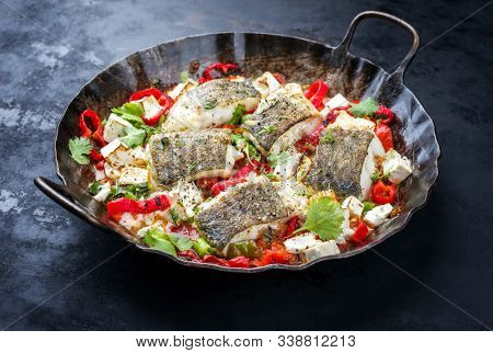 Traditional fried Greek cod fish filet casserole with feta cheese and vegetable as closeup in a rustic wrought iron pan