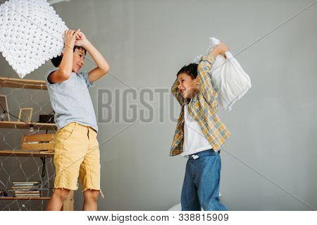 Cute Tween Boys Playing With Pillow On The Parents Bed At Home