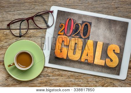 2020 goals - New Year resolution concept - word abstract in vintage letterpress wood type blocks against grunge metal background on screen of a digital tablet with a cup of coffee