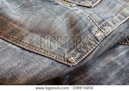 Blue Shabby Jeans. Texture Denim. Torn Fabric. Close-up Of Patch Pocket And Classic Sewing Stitches.