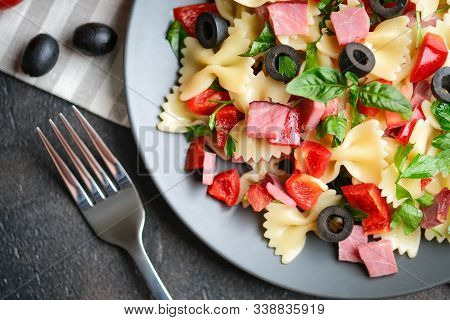 Traditional Salad With Pasta Farfalle, Ham, Pepper And Herbs On A Dark Plate On A Dark Background To