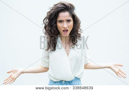 Mad Exaggerated Woman Gasping, Spreading Hands And Asking Question. Wavy Haired Young Woman In Casua