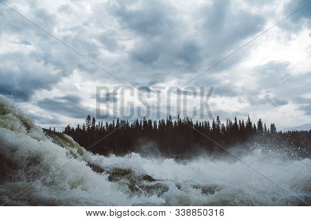 Waves And Splashes Of Mountain River On Background Of Forest, Rocks And Dramatic Sky. Forest River W