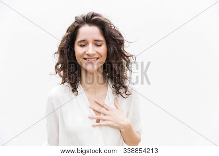 Happy Grateful Pretty Woman With Closed Eyes Applying Hand To Chest. Wavy Haired Young Woman In Casu