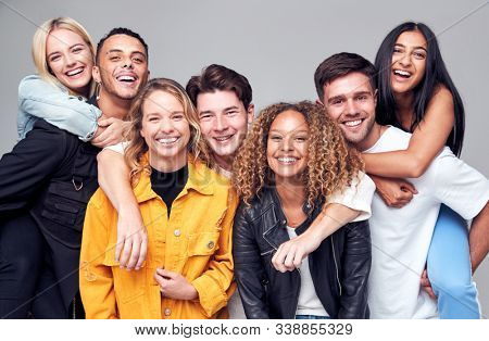 Group Studio Shot Of Young Multi-Cultural Friends Giving Each Other Piggybacks And Smiling At Camera