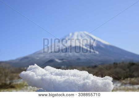 A Hand Clenching The Snow Against The Background Of Mount Fuji