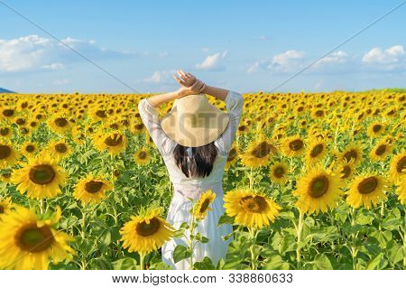 Portrait Of Happy Asian Woman Enjoying And Relaxing In A Full Bloom Sunflower Field During Travel Ho