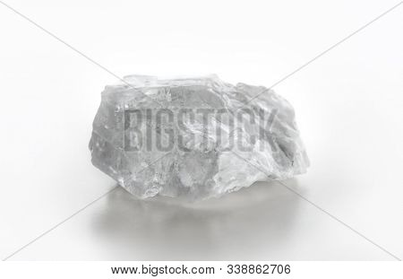 A chunk or crystal of Himalayan rock salt also  known as Halite. Isolated on neutral white with natural shadows.