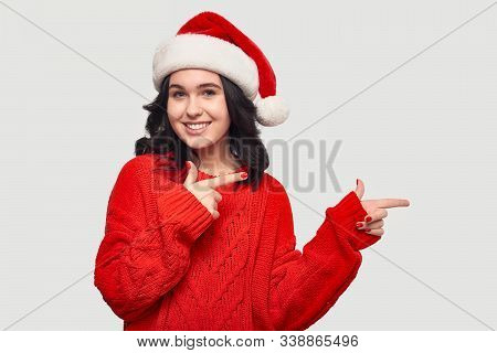 Pretty Brunette Girl In A Red Sweater And Santa Hat Pointing At The Copy Space Isolated Over Grey Ba