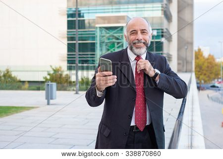 Happy Successful Mature Company Owner With Smartphone Adjusting Tie. Elderly Man In Formal Suit And