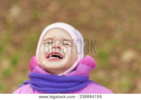 Portrait Of 2-3 Years Old Girl In Pink Warm Autumn Clothes And Violet Scarf Crying With Closed Eyes.