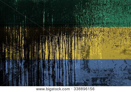 Gabon Flag Depicted In Paint Colors On Old And Dirty Oil Barrel Wall Closeup. Textured Banner On Rou