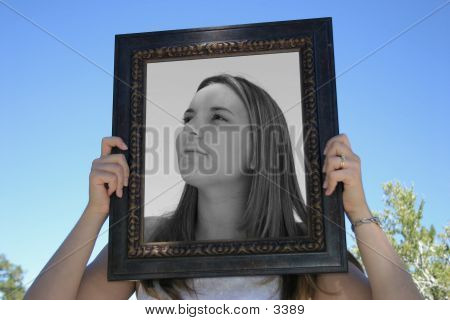 A young woman inside a picture frame. poster