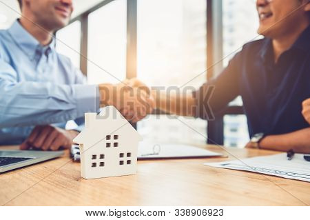Closeup Of Real Estate Broker Agent Shaking Hands With Customer After Signing Contract Agreement Doc