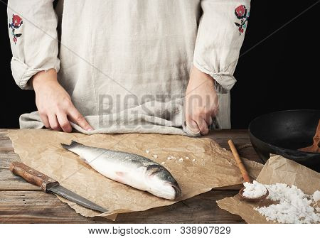 Fresh Whole Sea Bass Fish Lies On The Table, Cooking Process, Dark Background