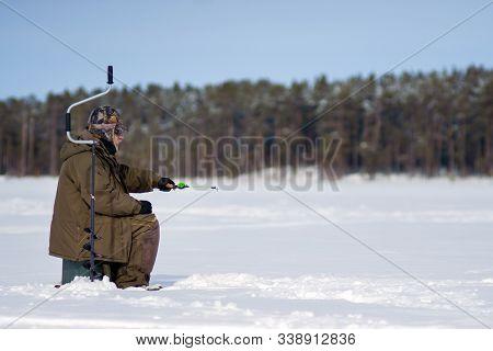 Winter Fishing. Ice Fisherman Fishing In The Winter On The River. Winter Fisherman Sits In Camouflag