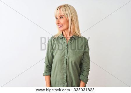 Middle age woman wearing green casual shirt standing over isolated white background looking away to side with smile on face, natural expression. Laughing confident.