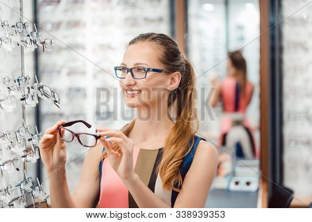 Beautiful woman choosing new glasses in store being yet undecided