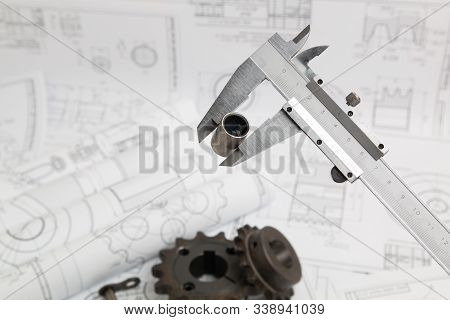 Metal Cylinders And Calipers On Printed Engineering Drawings. Mechanics And Engineering Technology.